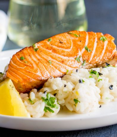 Feature image showing the crispy seared salmon and a creamy lemon risotto.