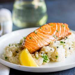 Seared salmon on a bed of lemon risotto on a white plate