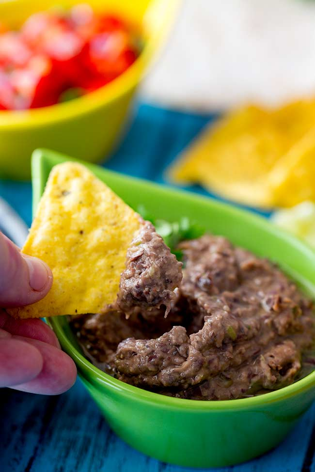Green bowl of black bean dip lithesome using a tortilla chip to scoop some out.