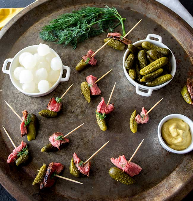Overhead view of a metal tray with lots of dill pickle beef skewers on it.