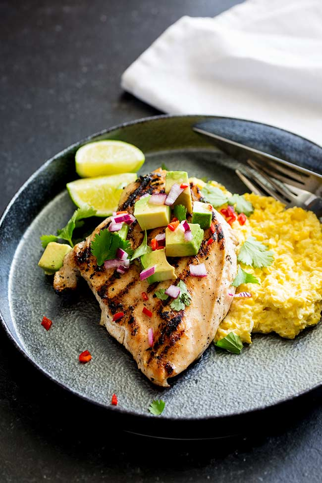 Overhead view showing the garnishes on the char grilled chicken. Choped avocado, red onions, red chilli and fresh cilantro.