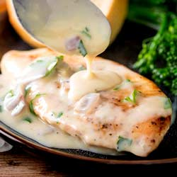 SQ picture showing creamy champagne sauce being drizzled over a crispy chicken breast fillet