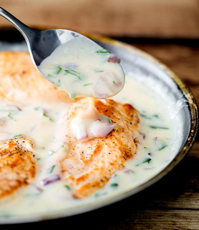 A spoonful of the creamy champagne sauce being drizzled over a chicken breast