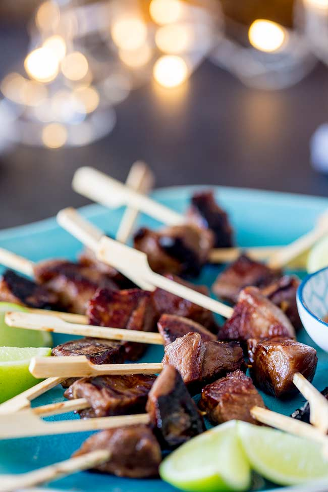 Dark red brown lamb cubes on small wooden skewers on a blue plate with fairy lights in the background