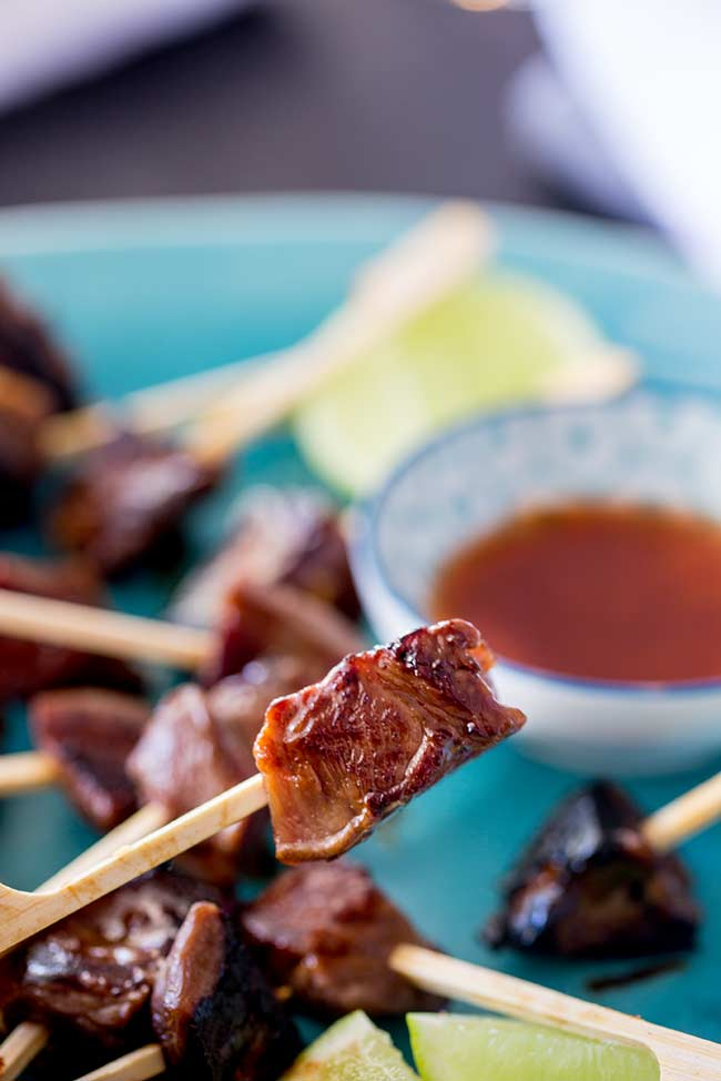 Close up on a Mongolian lamb skewer being lifted from the plate.