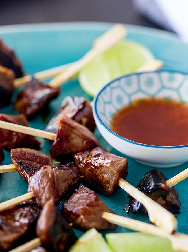 Overhead shot showing a big pile of lamb skewers on a turquoise blue oriental style plate.