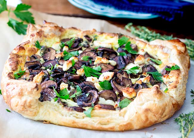 close up showing the golden puffed pastry of this mushroom tart.
