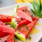 Stacked wedges of watermelon with black salt on them on a white plate.