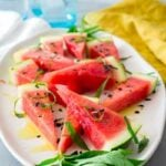 A SQ overhead shot of salted watermelon on a white plate, with a yellow napkin and blue glasses