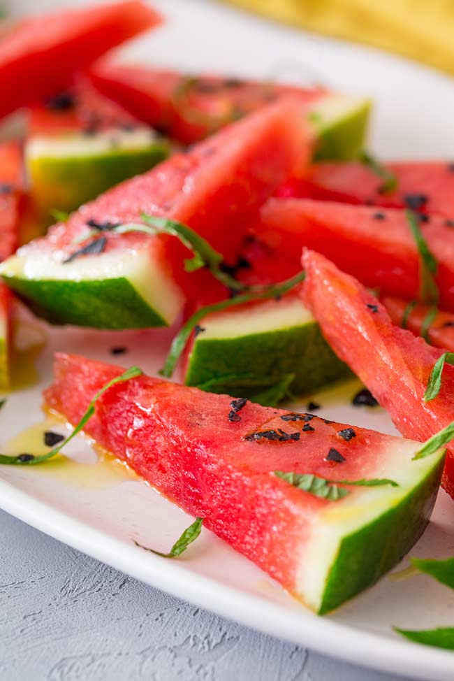 Close up on the flesh of the watermelon wedge with black salt and mint garnishing it.