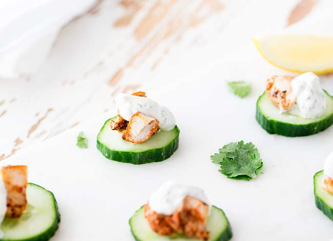 thin cucumber dish with a small piece of tandoori chicken on it, drizzled with a mint yogurt