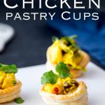 Pinterest image, White platter with pastry cups filled with curried chicken and text at the top