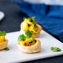 SQ picture, curried chicken cup on a white platter with blue napkin in the background