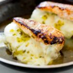sq picture of two dill pickle and provolone stuffed chicken breasts in a frying pan.