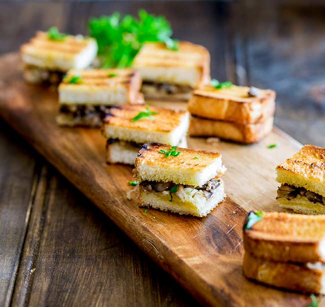 8 mini grilled cheese sandwiches on a wooden board garnished with parsley