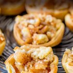 Pinterest image showing an individual mini apple pie with a bite out of it and text at the top