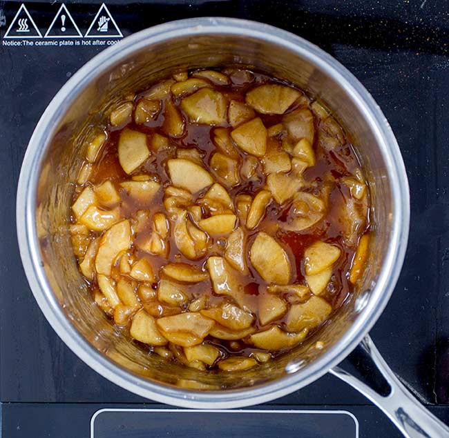 Silver pan filled with a golden apple pie mixture