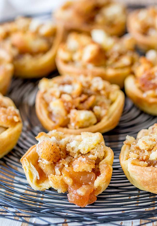 Close up on a mini apple pie with a bite out of it, showing the apple filling.