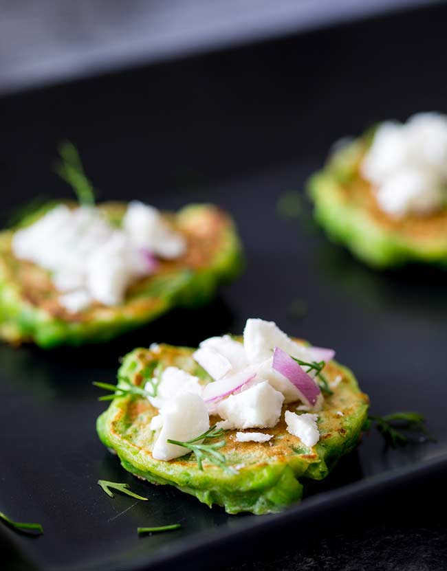 Black plate and a close up on a single green pea fritter, showing the bright colour and the white goats cheese cream