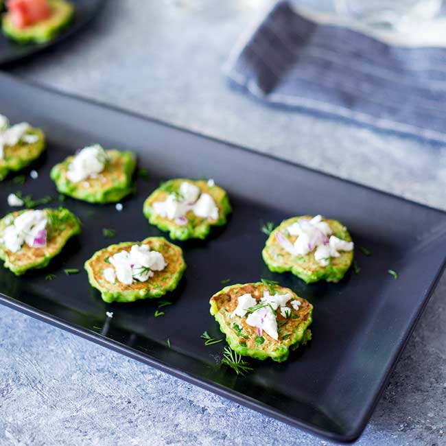 Table view showing a platter of these pea fritters on a black plate on a concrete bench.