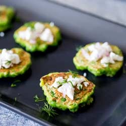 SQ photo of 4 pea fritters on a rectangular black plate