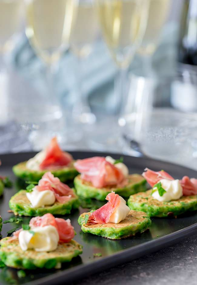 table view showing the black plate of pea bites with champagne flutes in the background