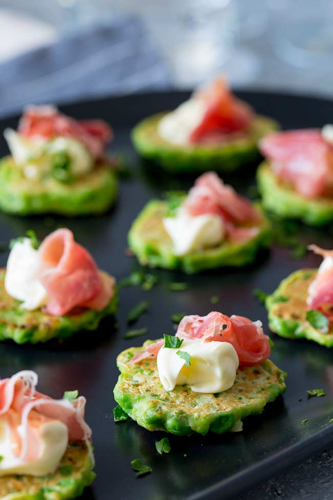 8 bright green pea bites with prosciutto on top sat on a black plate scattered with parsley
