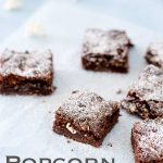 Pinterest image, 6 popcorn brownies on a sheet of parchment paper on a blue table, text at the bottom of the image
