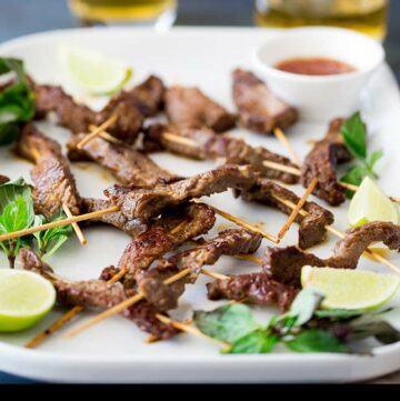 Thai beef skewers on a white platter, garnished with thai basil and lime segments