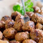 pinterest image showing a beef meatball on a fork with text at the top of the image