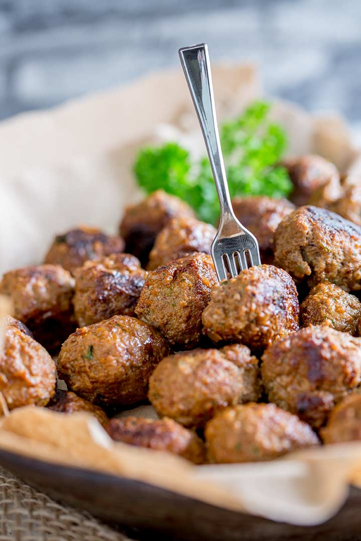 Pile of meatballs in a metal bowl with a fork in a meatball