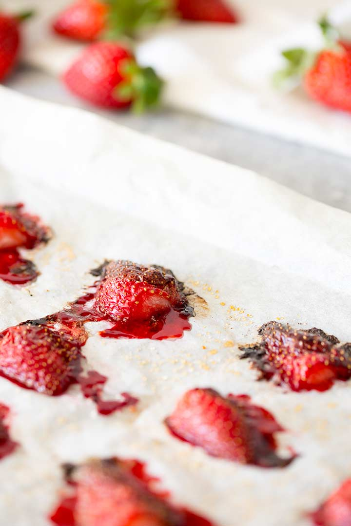 lined tray of roasted strawberries with fresh ones in the background
