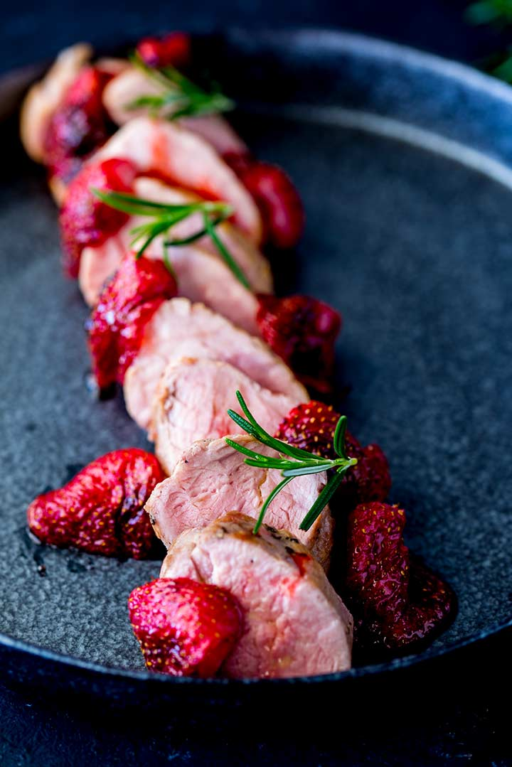 overhead view showing slices of rosemary pork tenderloin on a black plate with roasted strawberries and rosemary garnish
