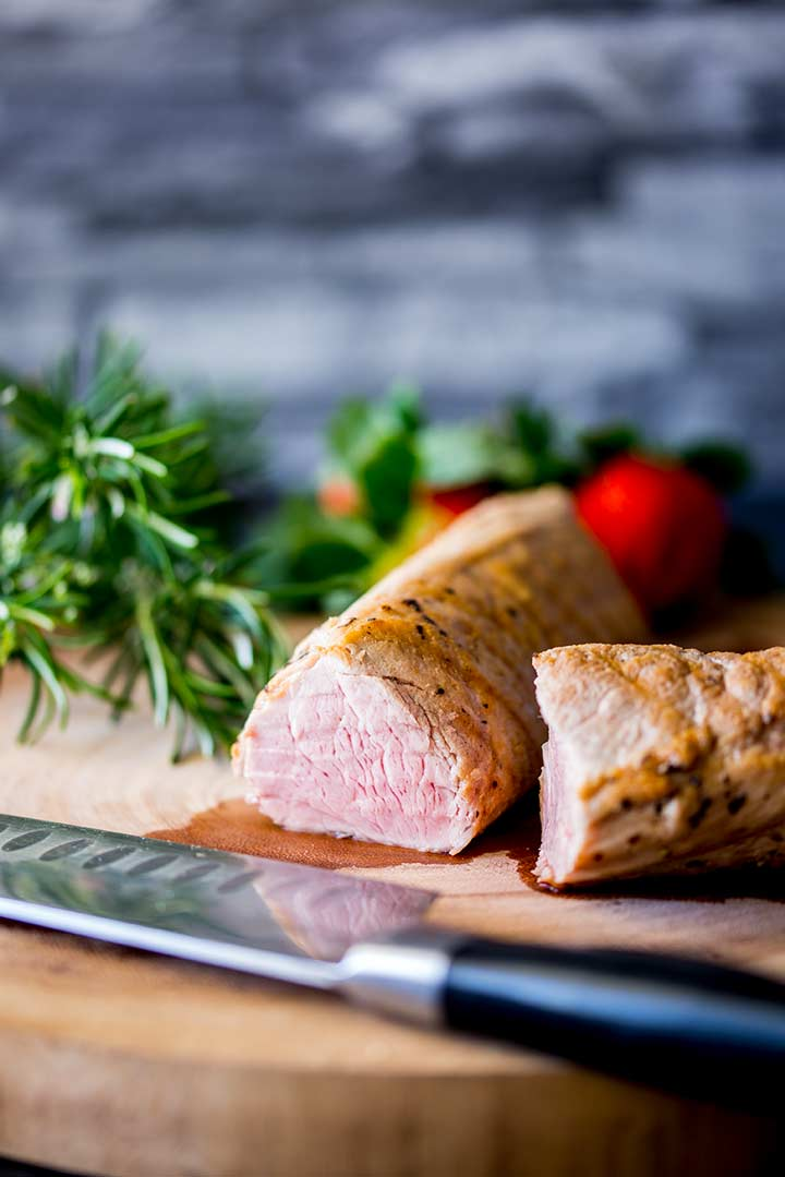 Cooked rosemary Pork tenderloin before slicing, sat on a wooden chopping board with rosemary in the background.