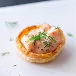 Single shrimp cocktail pastry cup on a white plate garnished with dill