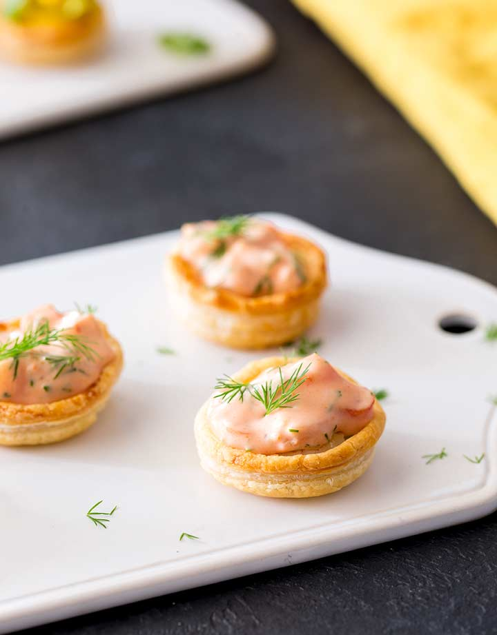 3 shrimp cocktail pastry cups sat on a white tray with a yellow napkin behind