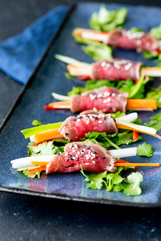 showing the vegetables inside the beef tataki rolls plus the bed of cilantro leaves