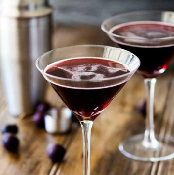 SQ shot showing two martini glasses with a dark red cherry martini in them