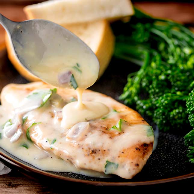 A black plate with a chicken fillet on it and creamy sauce being drizzled over it from a silver spoon