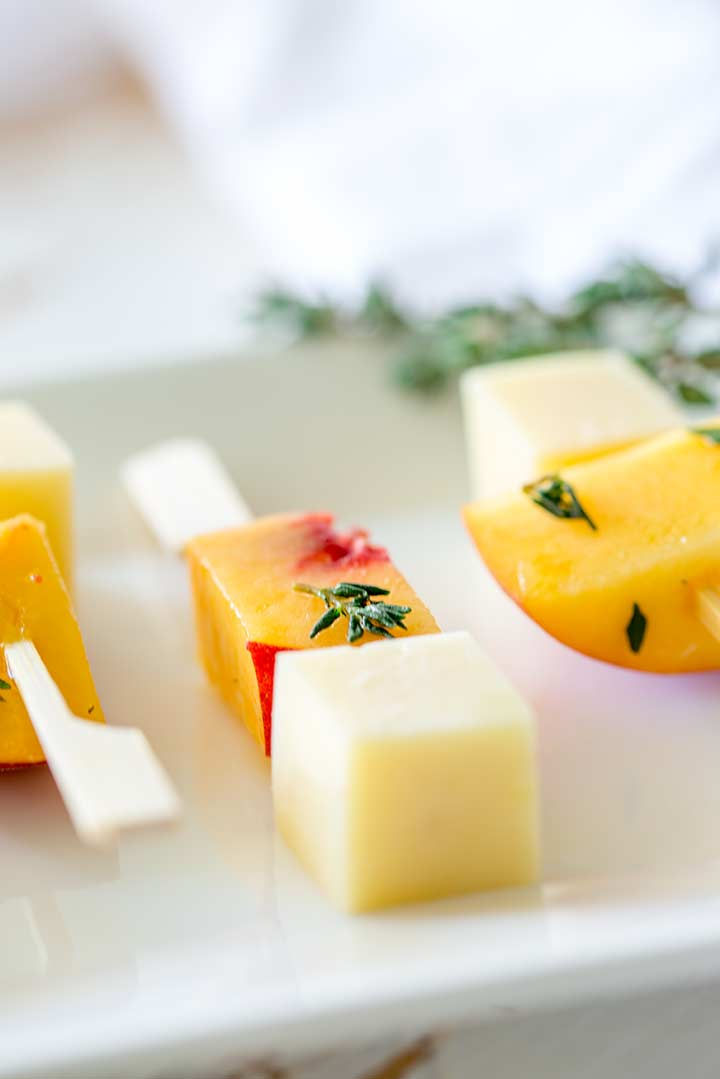close up on the cube of peach with fresh thyme on these gouda and peach skewers
