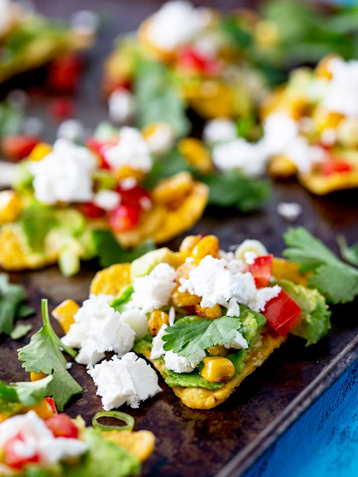 close up showing the charred corn and chopped tomato on these fully loaded tortilla chips