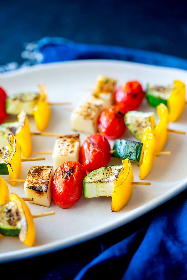 Head on view showing the halloumi and vegetable kebabs on a white platter on a blue table