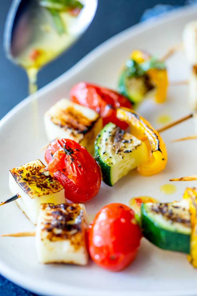 Close up on a halloumi and vegetable skewer showing the dressing being drizzled over