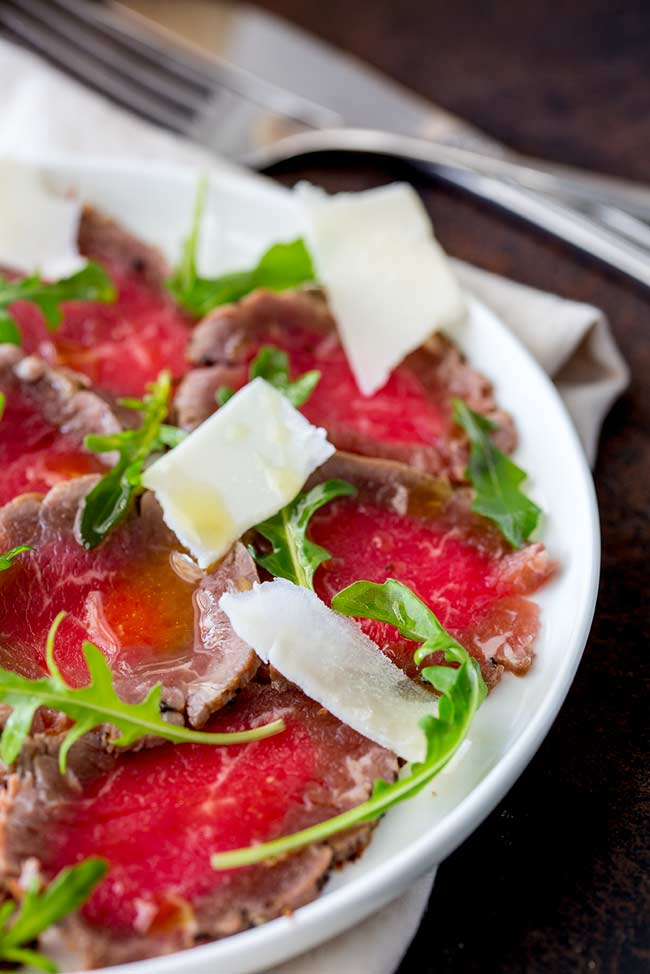 overhead view of thin slices of beef carpaccio on a white plate, garnished with arugula and parmesan