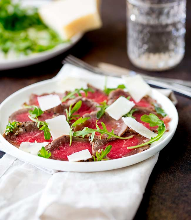 Table view showing a white plate of seared pepper beef carpaccio, with arugula and parmesan in the background