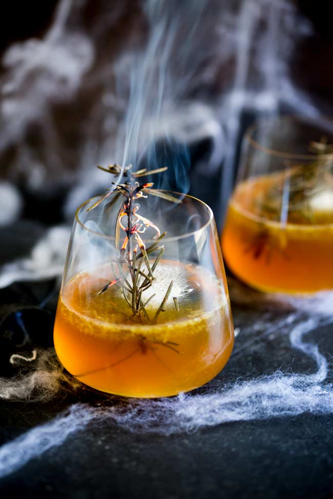 Black table with cobwebs, whisky glass with orange liquid and a smoking twig of rosemary