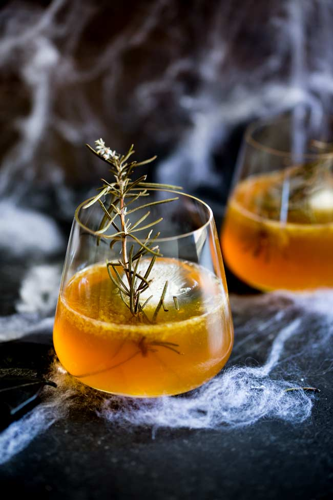 black table with cobwebs showing two bourbon cocktails garnished with rosemary twigs