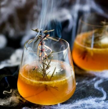 close up on a smoking sprig of rosemary in a bourbon cocktail