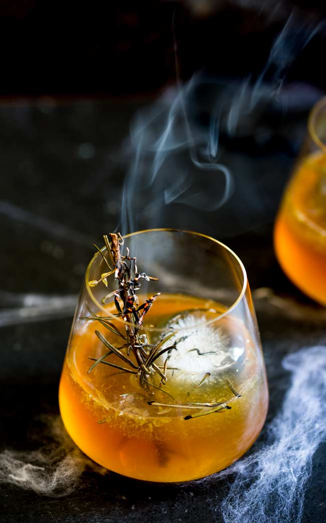 Black table with a whisky glass filled with orange liquid and a giant round ice 'cube'