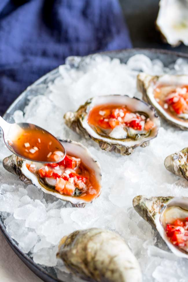a spoonful of the pink mignonette dressing being drizzled over an oyster sat on a bed of ice